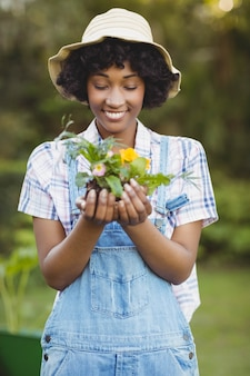 Smiling woman holding flowers in the garden