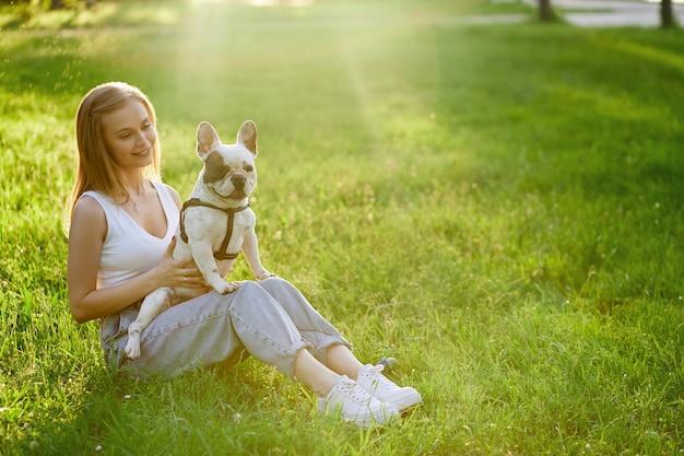 草の上にフレンチブルドッグを保持している笑顔の女性