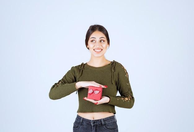 Donna sorridente che tiene il contenitore di regalo e che guarda l'obbiettivo su sfondo bianco.