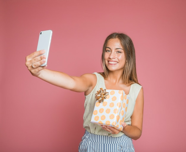 Smiling woman holding gift box taking selfie from cellphone against pink background