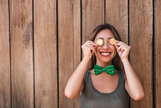 Smiling woman holding golden coins near eyes