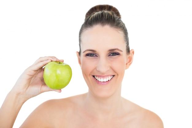 カメラを見ている緑色のリンゴを持つ笑顔の女性