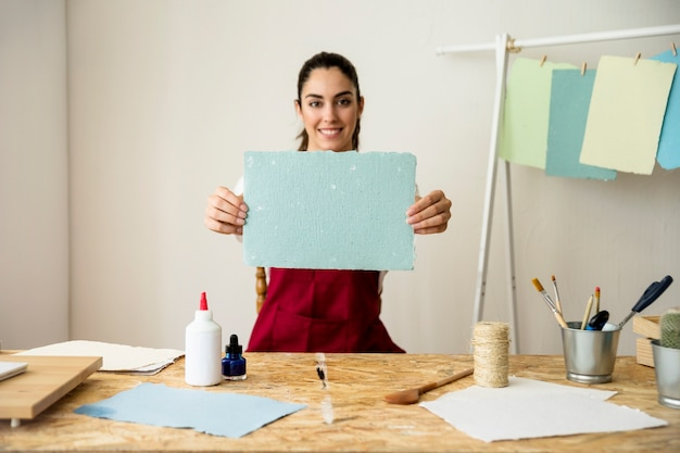 Smiling woman holding handmade blue paper