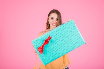 Smiling woman holding large gift box with red bow against pink background