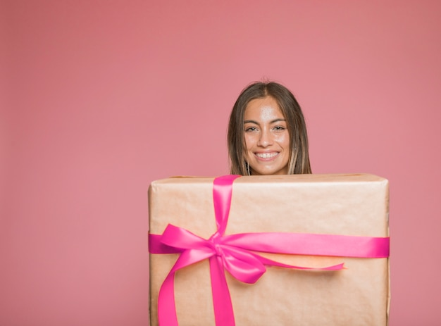 Smiling woman holding large gift box wrapped with pink bow against colored background