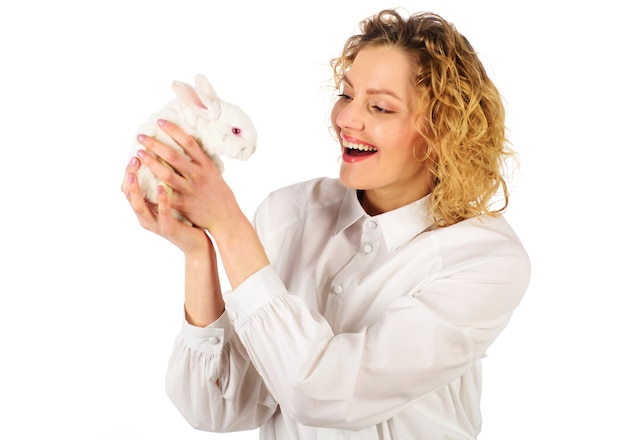 Smiling woman holding a little white rabbit on white background.