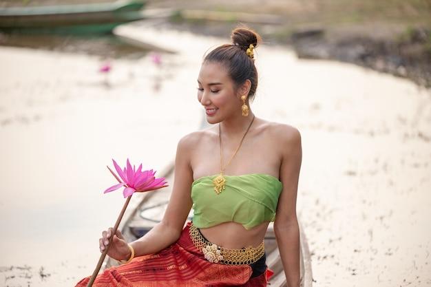 Smiling woman holding lotus while sitting on boat in lake