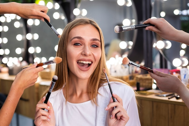 Smiling woman holding make-up brushes