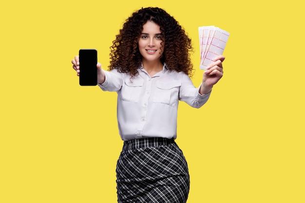 携帯電話と宝くじを持っている笑顔の女性。オンラインカジノ、宝くじ、スポーツ賭博のコンセプト。