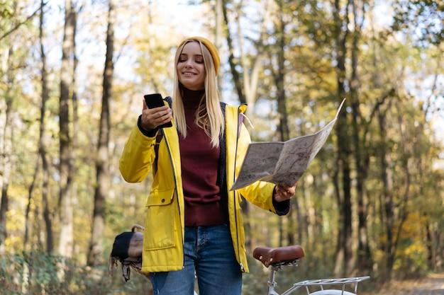 Улыбающаяся женщина держит мобильный телефон с помощью карты для навигации в осеннем лесу.