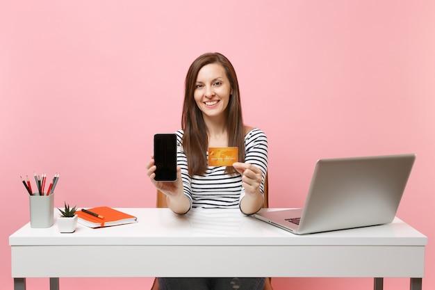 Улыбающаяся женщина, держащая мобильный телефон с пустым экраном, кредитная карта сидит за белым столом с современным пк, изолированным на пастельно-розовом фоне. достижение деловой карьеры. скопируйте пространство.