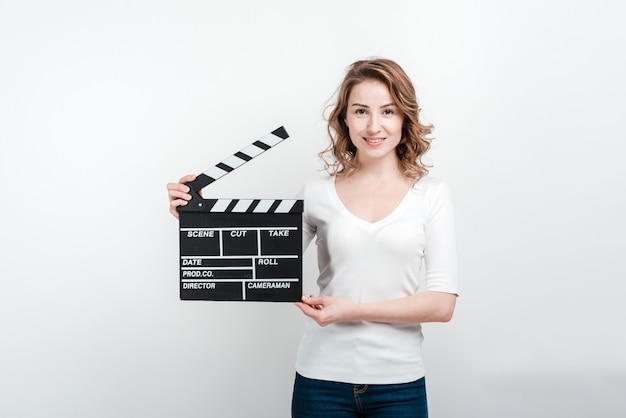 Smiling woman holding movie board.