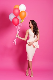 Smiling woman holding multi colored balloons