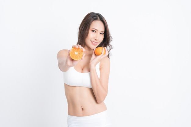 Smiling woman holding orange juice and fruit