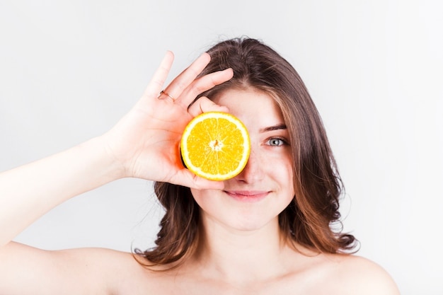 Smiling woman holding orange slice at face