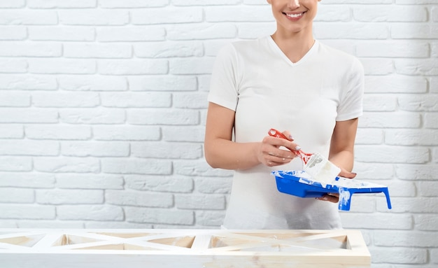 Smiling woman holding paint near rack