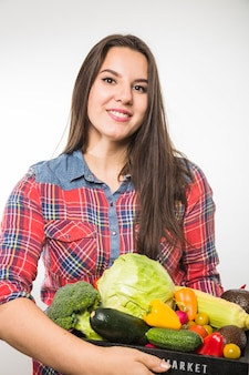 Smiling woman holding pallet with vegetables