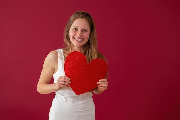 赤い背景の上の手でパッパーハートを保持している笑顔の女性