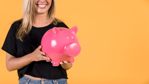 Smiling woman holding pink piggy bank against bright backdrop