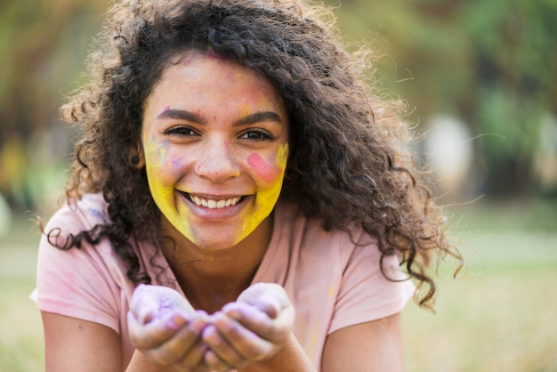 Smiling woman holding powdered paint in her hands