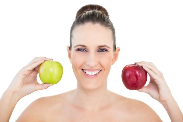 赤と緑のリンゴを持つ笑顔の女性