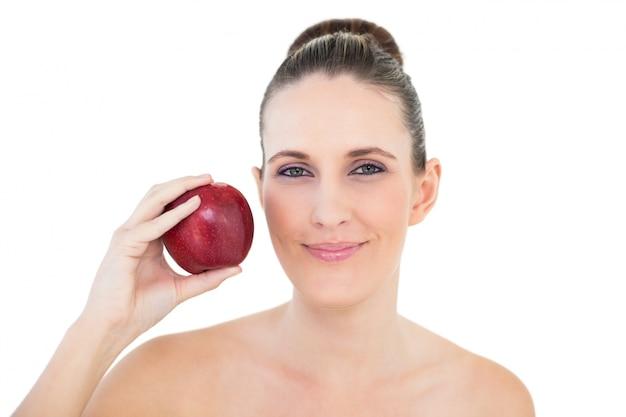 カメラを見ている赤いリンゴを持っている笑顔の女性