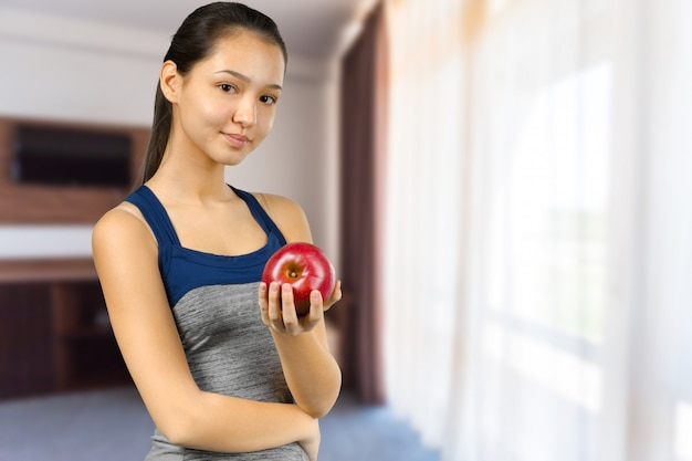 Smiling woman holding red apple