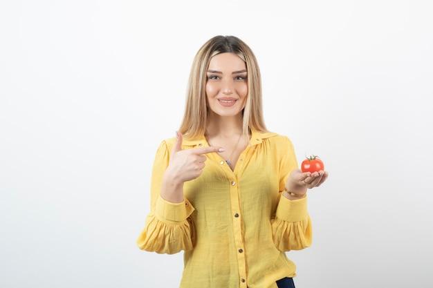 Donna sorridente che tiene pomodoro rosso e posa su bianco.