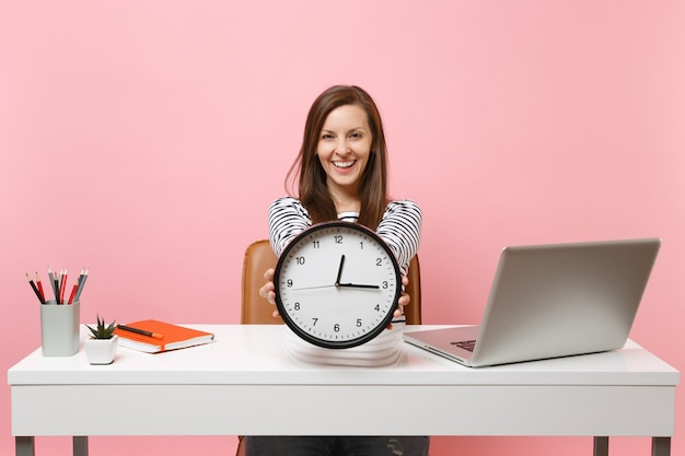 Smiling woman holding round alarm clock while sit and working on project at white desk with contemporary pc laptop