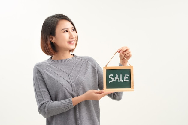 Smiling woman holding sale sign isolated over white