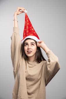 灰色の背景にサンタの帽子を頭上に保持している笑顔の女性。