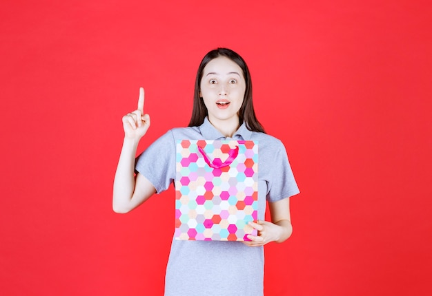 Smiling woman holding shopping bag and point finger up