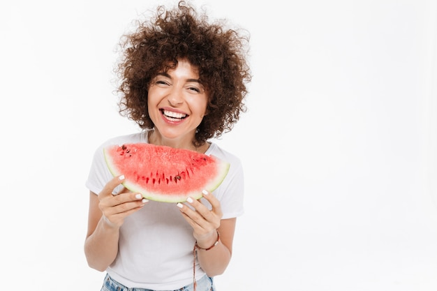 Smiling woman holding slice of a watermelon and laughing