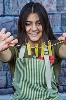 Una donna sorridente che tiene le fette di ananas su sfondo blu