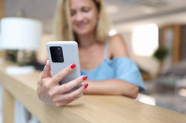 Smiling woman holding smartphone in hands mobile dating apps concept