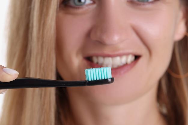 彼女のクローズアップの前に歯ブラシを保持している笑顔の女性