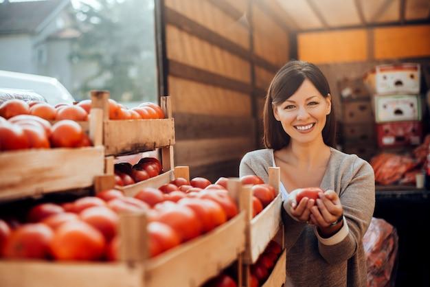 グリーンマーケットで野菜を持って笑顔の女性。