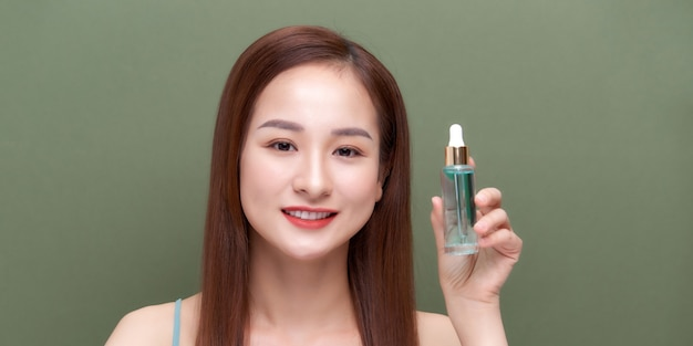 Улыбающаяся женщина, держащая сыворотку витамина c возле ее лица на зеленом фоне