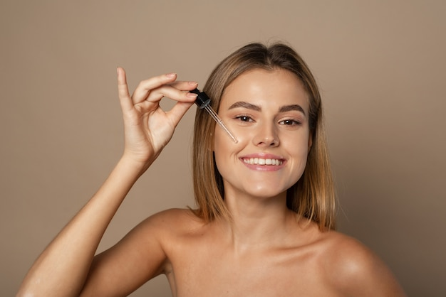 Smiling woman holding vitamin c serum near her face