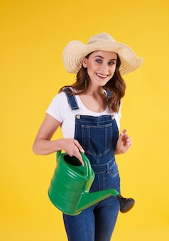 Smiling woman holding watering can in studio shot