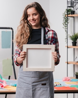 Smiling woman holding white empty picture frame looking at camera