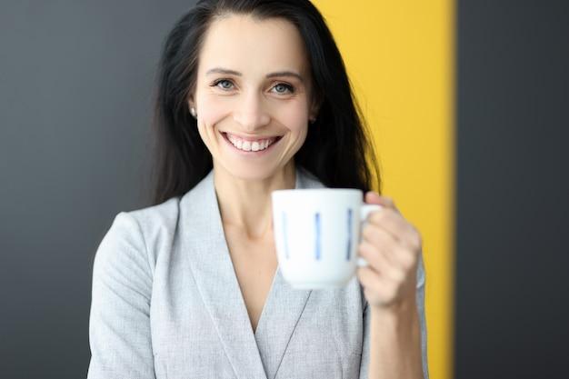 Улыбающаяся женщина, держащая белую кружку в руках на рабочем месте, ломает концепцию