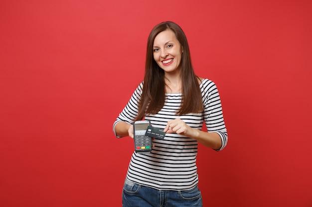 신용카드 결제를 처리하고 획득하기 위해 무선 현대식 은행 결제 단말기를 들고 있는 웃고 있는 여성, 빨간색 배경에 격리된 검은색 카드. 사람들은 진실한 감정, 라이프 스타일. 복사 공간을 비웃습니다.