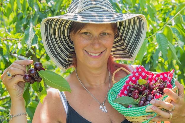 新鮮な熟したサクランボと木箱を保持している笑顔の女性