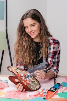 Smiling woman holding wooden messy palette and paintbrush looking at camera
