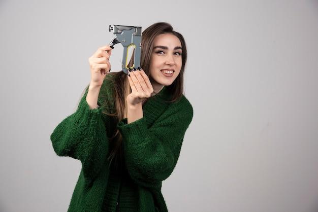 Donna sorridente che tiene uno strumento di lavoro su uno sfondo grigio.