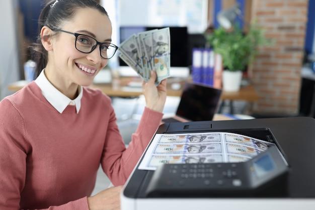 Улыбающаяся женщина держит в руках банкноты и печатает их на принтере. концепция увеличения денежных вложений