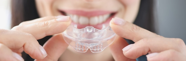 Smiling woman holds clear plastic mouthguard to straighten teeth