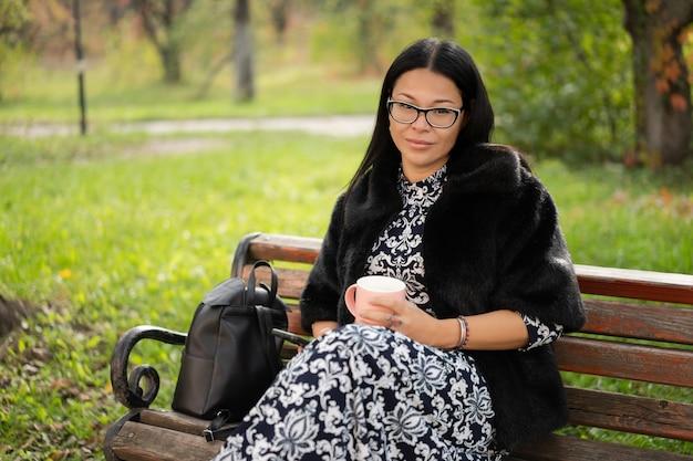 웃는 여자는 화창한 날에 야외에서 편안한 커피 컵을 보유하고있다. 모피 코트를 입고 아름다운 아시아 아가씨