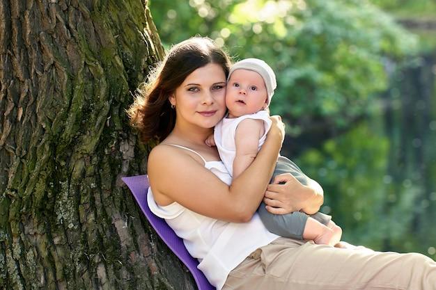 笑顔の女性は、屋外を歩いている間、彼女の小さな子供を保持します